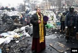 Революція гідності. Священник молиться на одній з барикад під час чергового дня антиурядового протесту в Києві, 28 січня 2014 року
