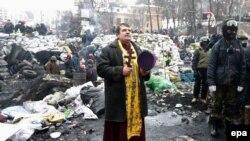 Священик молиться на одній з барикад під час чергового дня антиурядового протесту в Києві, 28 січня 2014 року