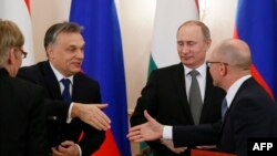 Russian President Vladimir Putin (2nd right) looks on as Hungary's Prime Minister Viktor Orban (left) shakes hands with Russia's nuclear agency Rosatom head Sergei Kiriyenko (right) during a meeting at the Novo-Ogaryovo residence outside Moscow on January 14.