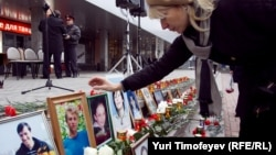 A woman places a photo at a commemoration ceremony for the victims at the Dubrovka Theater in Moscow on the event's ninth anniversary on October 26.