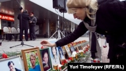 A woman looks at photographs of victims at a commemoration ceremony recalling the Dubrovka theater in Moscow, which resulted in 130 deaths.
