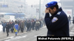 A policeman in Sarajevo looks on as retired Bosnian joint-army soldiers march in December for pension benefits.