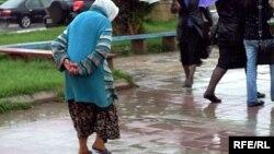 Arxiv fotosu: Bakıda yağış altında yaşlı qadın.