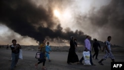 Displaced Iraqi families arrive near a checkpoint east of Mosul as they flea areas of unrest on October 22.