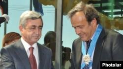 Armenia -- President Serzh Sarkisian gives a Medal of Honor to UEFA President Michel Platini, 1Sept 2010.