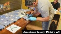 Полицейский вскрывает упаковки с кокаином в посольстве России в Аргентине, декабрь 2016 года