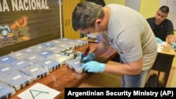 A police officer opens up a package of cocaine found in an annex building of the Russian Embassy in Buenos Aires in December 2016.