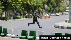 A Revolutionary Guard moves during the attack on parliament in the center Tehran June 7.