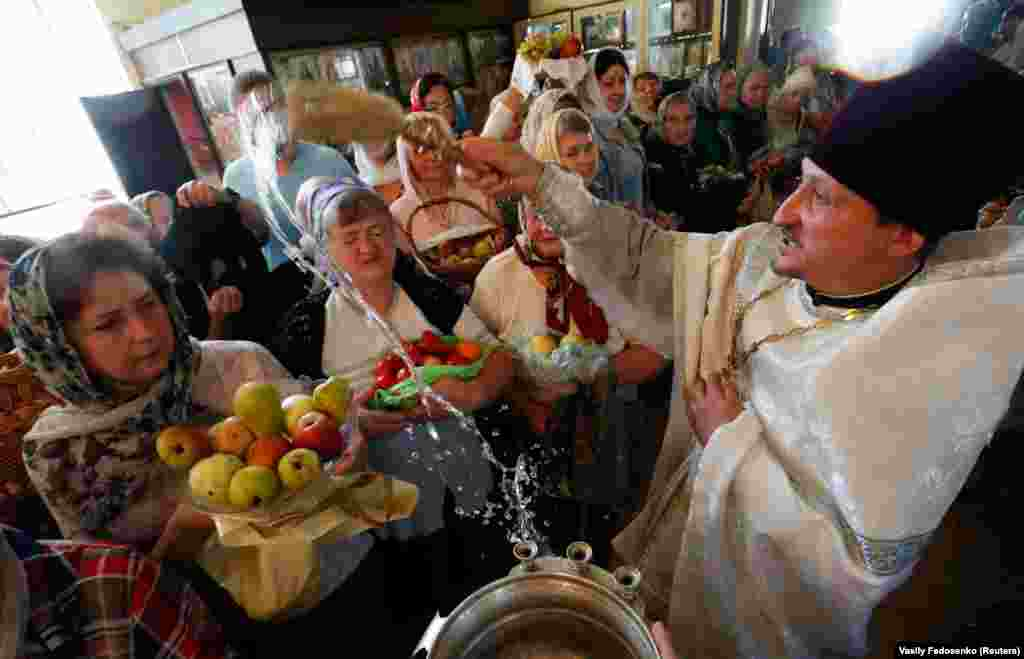 An Orthodox priest blesses apples and pears in a church during the Yablochniy Spas, or Apple Feast of the Savior, a religious holiday in Bobruisk, Belarus, on August 19. (Reuters/Vasily Fedosenko)