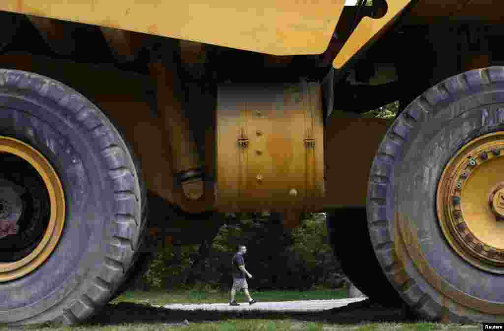 A man passes by an old dump truck used in mining operations.