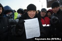 Участник акции протеста показывает требования протестующих. Актау, 19 декабря 2011 года