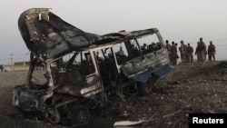 Afghan security force inspect the wreckage of a bus hit by a suicide car-bomb attack in Kandahar Province on July 2