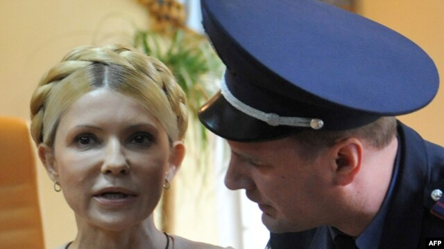 A police officer tries to calm Yulia Tymoshenko as she reacts to the verdict.