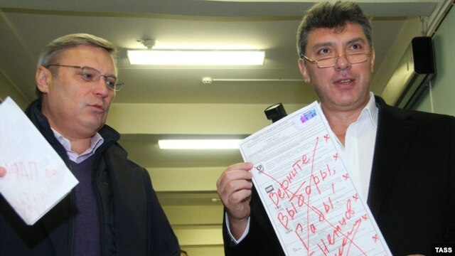 Opposition leaders Mikhail Kasyanov (left) and Boris Nemtsov show their defaced ballots during parliamentary elections at a polling station in Moscow in December 2011.