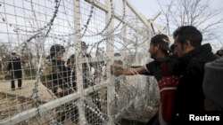 FILE: Refugees and migrants stand next to a border fence at the Greek-Macedonian border.