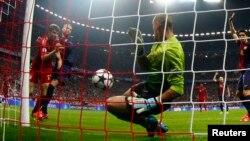 Нападник «Баварії» Томас Мюллер (ліворуч у червоній формі) забиває перший гол у ворота «Барселони», які захищає Віктор Вальдес