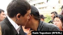 Один мужчина что-то шепчет другому на ухо во время митинга в Алматы. Иллюстративное фото.