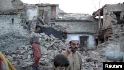 Residents walk past the rubble of a house after it was damaged by an earthquake in Mingora, Swat on October 26.