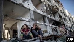 Брати палестинці сидять побіля розбомбленого будинку, Смуга Гази 5 серпня