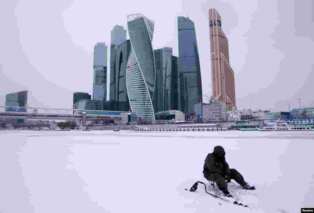 "A man fishes on the ice-covered Moskva River near the Moscow International Business Center, also known as ""Moskva-City,"" in Moscow. (Reuters/Maksim Zmeyev)"