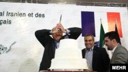 یکی از اعضای هیئت تجاری فرانسه در اتاق بازرگانی تهران، کیک مراسم همنشینی فعالان اقتصادی ایران و فرانسه را میبرد