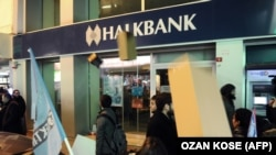 Protestors throw shoe boxes at the entrance of a Halkbank bank branch in the Besiktas district of Istanbul on December 19, 2013.