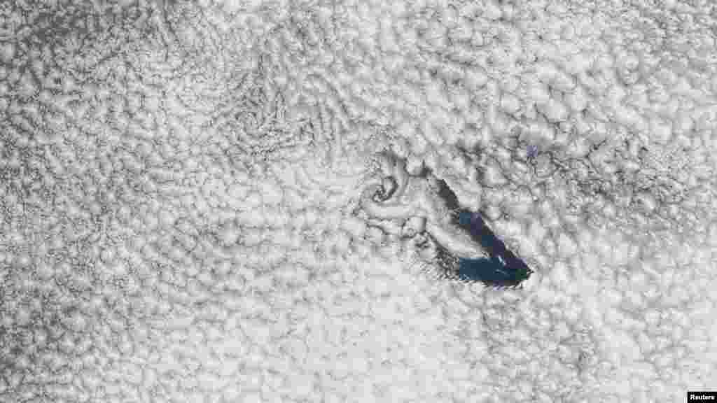 A NASA imaging spectroradiometer aboard an orbiting satellite captured this true-color image of St. Helena Island and a band of wind-blown cloud vortices trailing toward the island's leeward side over the South Atlantic Ocean. Tiny St. Helena lies approximately 1,900 kilometers west of Africa. (Reuters/NASA)