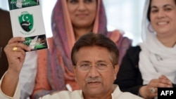 Former President Pervez Musharraf holds a copy of his party manifesto at his residence in Islamabad on April 15.