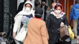 Iranian women wearing face mask walk past in a street of Tehran, Iran, 26 February 2020.