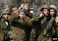 Ізраїльські військові виносять пораненого внаслідок нападу товариша, 28 січня 2015 олку