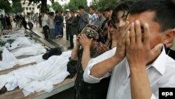 Люди молятся около тел жертв расстрела в Андижане. 14 мая 2005 года.