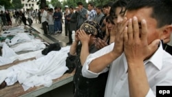 People pray over the bodies of victims of the government crackdown in Andijon on May 14, 2005. It's still not known whether hundreds or thousands died in the violence.