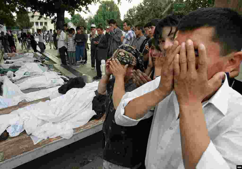 Locals pray in front of the bodies of those who died in the fighting on May 13 - The deadly encounter between Uzbek security forces and demonstrators still has not been fully documented.