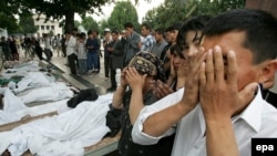 People pray on May 14, 2005, by the bodies of victims of the government crackdown in Andijon.