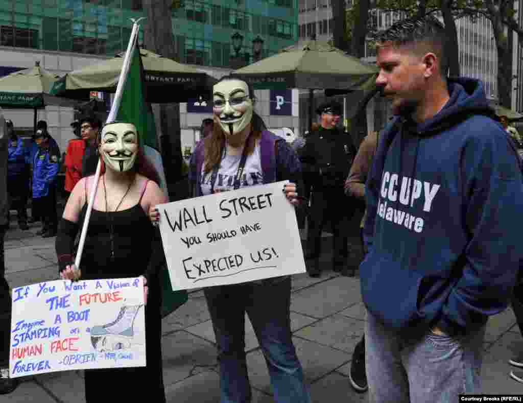 "Three OWS activists protest at New York City's Bryant Park. Many protesters wore masks from the movie ""V For Vendetta,"" a dystopian thriller in which London is a police state."