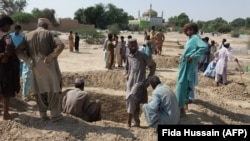 Mourners dig graves for the victims of a suicide blast outside the Sufi shrine in Jhal Magsi district in Balochistan on October 6.