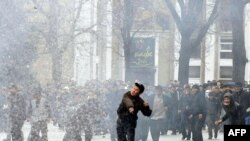 Antigovernment protesters throw stones at Kyrgyz policemen and servicemen in Bishkek on April 7, 2010.