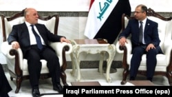 Iraqi parliament speaker Salim al-Jubouri (right) meets with Iraqi Prime Minister Haidar al-Abadi in Baghdad on September 27.