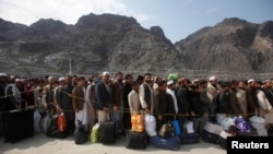 Afghan citizens wait to cross into their home country at the border post in Torkham on March 7.