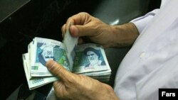 An Iranian man counts rials.