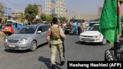 Afghan police officers stop cars at a check point in Herat on September 27.