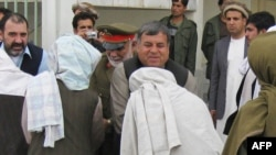 Kandahar Governor Tooryalai Wesa (facing camera) greets Taliban fighters as they surrender arms during a meeting with Afghan government officials as part of the government's peace and reintegration process in Kandahar on April 11.