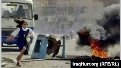 طفلة تركض بعيداً عن إطارات مشتعلة في أحد شوارع الفلوجة