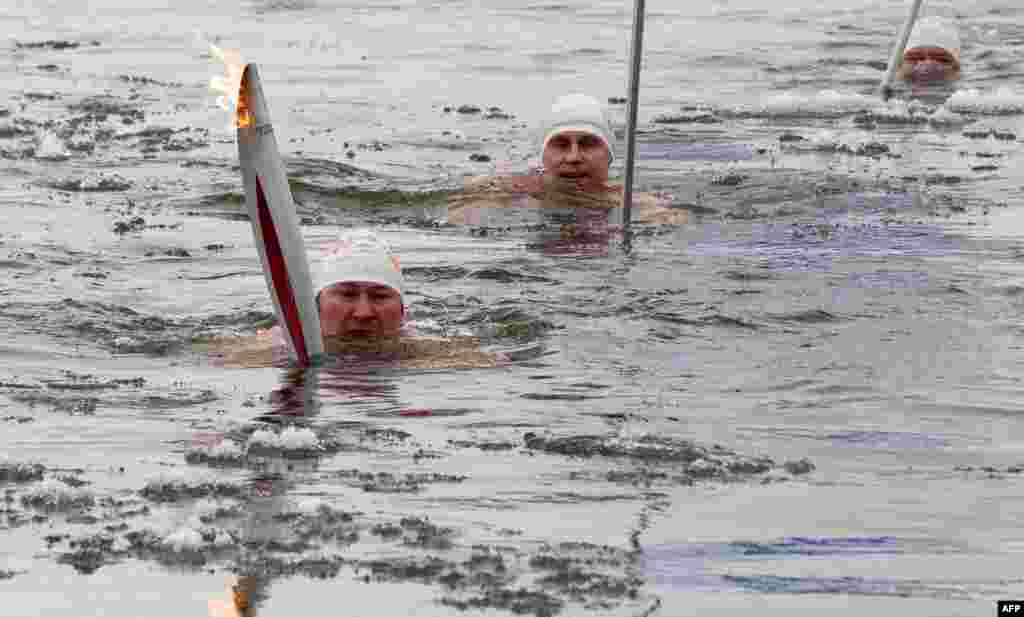Olympic torchbearer Aleksandr Brylin (left) swims with his torch in the company of other ice-swimmers in the Amur River in the Far Eastern Russian city of Blagoveshchensk. Russia is hosting the Winter Olympics in the Caucasus city of Sochi in 2014. (AFP)