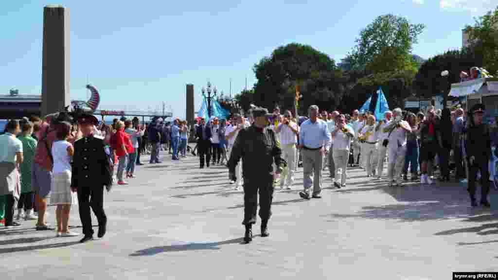 """Egizlerniñ yanında asker formalı adamlar. Kolonnanıñ yanında rusiye polisi hadimleri, """"Qırım samooboronası"""" hadimleri ve """"Qırım qazaqlığı""""nıñ vekilleri kete"""