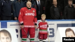 Belarus -- President Alyaksandr Lukashenka and his son Nikolay stand behind portraits of Marat Kalimullin (L) and Ruslan Salei during a commemorative event at the Minsk-Arena sports complex in Minsk.