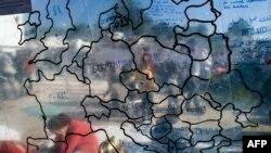 Карта Европы на фоне мигрантов и беженцев в лагере на греческом острове Лесбос. 16 октября 2015 года.