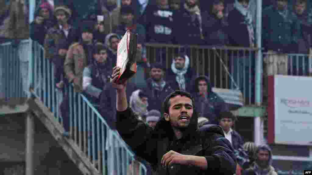 An Afghan demonstrator holds a copy of a half-burned Koran, allegedly set on fire by U.S. soldiers, at the gate of Bagram air base during a protest against Koran desecration at Bagram in February.