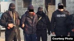 На распространенной 31 января 2018 года департаментом комитета национальной безопасности Южно-Казахстанской области фотографии — предположительно один из задержанных подозреваемых (второй слева) в окружении сотрудников силовых органов.