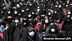 Iran Virus Outbreak Ashoura -- People wearing protective face masks to help prevent spread of the coronavirus mourn during an annual ceremony commemorating Ashoura, the anniversary of the 7th century death of Imam Hussein, a grandson of Prophet Muhammad,